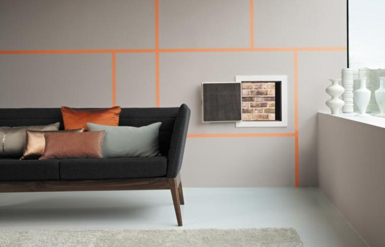 zona living dal design moderno ed essenziale con un divano grigio e pareti color tortora con righe arancio