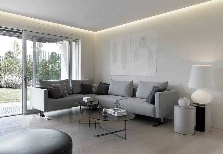 Mobili soggiorno con un divano grigio e due tavolini neri di metallo, pavimento parquet chiaro