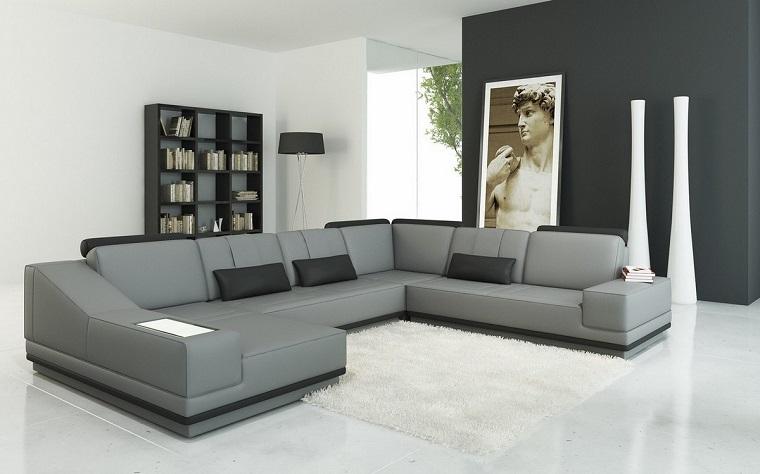 Idee arredo casa e un soggiorno con divano in pelle di colore grigio e cuscini neri