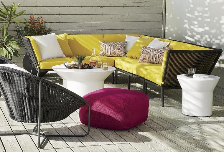 Piccoli giardini arredati con mobili in rattan, divano con sedute e schienali in tessuto di colore giallo