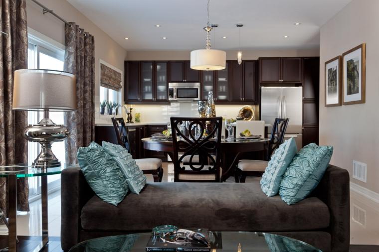 ambiente unico arredato in modo elegante con un divano marrone e cuscini turchesi, cucina a vista marrone