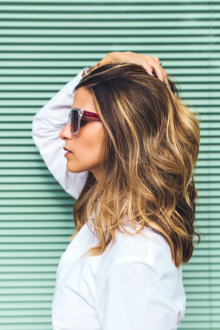 Capelli medi di una donna con acconciatura semplice di colore biondo con colpi di sole biondi