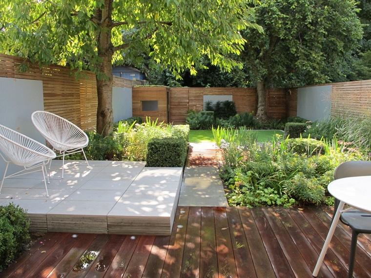 Recinzione giardino in legno e tanti alberi ornamentali da giardino, due sedie di colore bianco