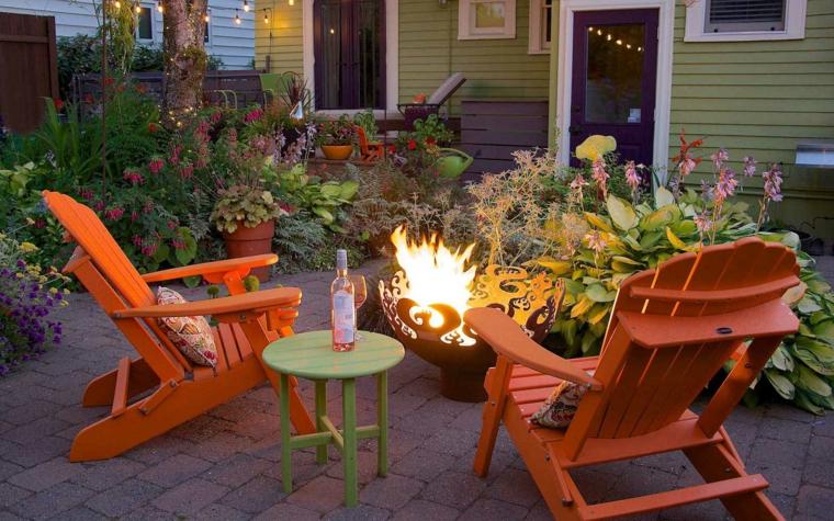 Idee giardino piccolo, arredamento con due sdrai di legno colore arancione e un tavolino intorno al fuoco
