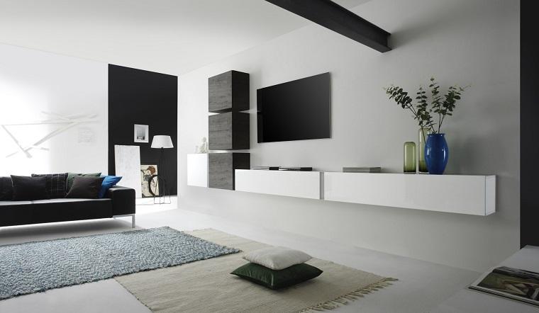 Come arredare un soggiorno con mobili sospesi e un divano nero, pavimento parquet e due tappeti di diverso colore