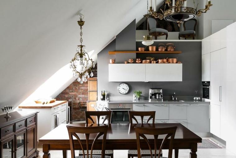 cucina con mobili e pensili bianchi, tavolo e sedie in legno, lampadari eleganti, arredare mansarda idee