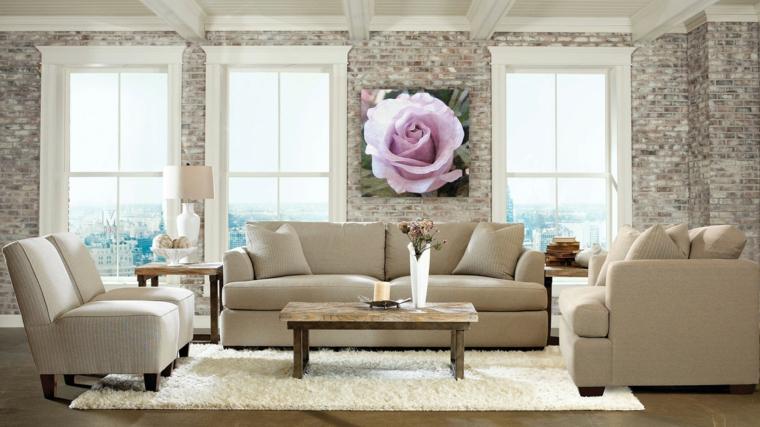 salotto arredato in stile elegante e moderno con divano e poltrone chiare, tappeto bianco e muri in pietra chiara