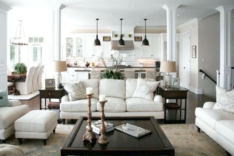 accogliente ed elegante salotto con divani bianchi tavolo quadrato con candelabri e cucina a vista