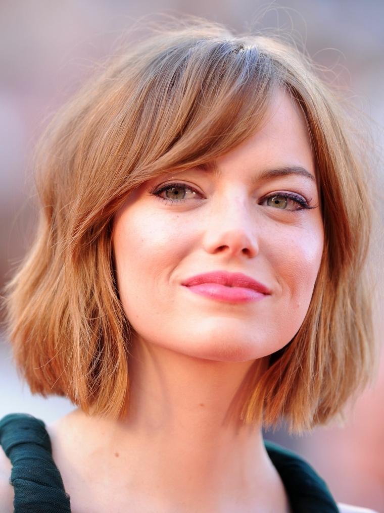 Idea per dei tagli capelli corti immagini, l'attrice Emma Stone con frangia e tinta di colore strawberry