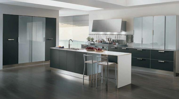 ampia e moderna cucina attrezzata con un'isola con lavello e tavolo con due sgabelli