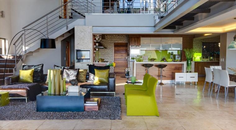 proposta originale open space moderni con soppalco con cucina con isola e sgabelli neri, divani verdi e neri