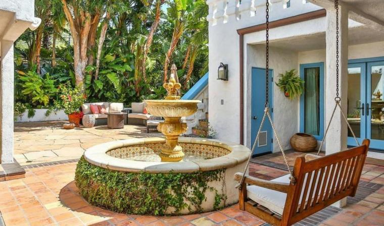Piante ornamentali da giardino, fontana dalla forma circolare e una panchina a dondolo