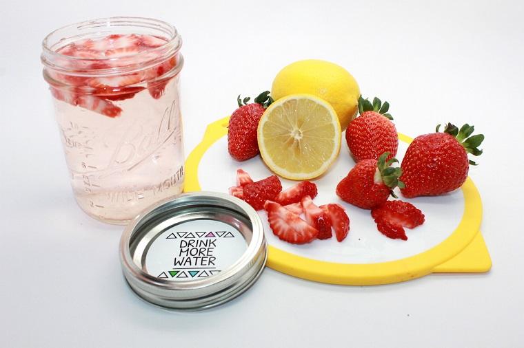 Bevande detox fai da te, barattolo di vetro con acqua aromatizzata alla fragola e limone