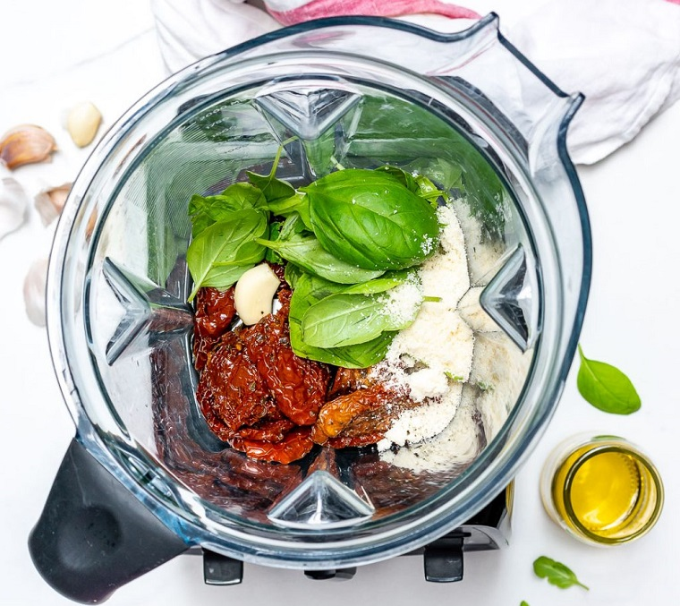 Secondi piatti estivi con la preparazione di un pesto di pomodori secchi in frullatore con basilico e parmigiano