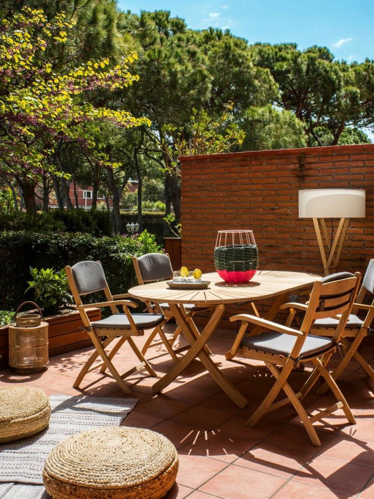 Piante da giardino fiorite, arredamento con mobili in legno e piccoli cuscini in vimini su cui sedersi