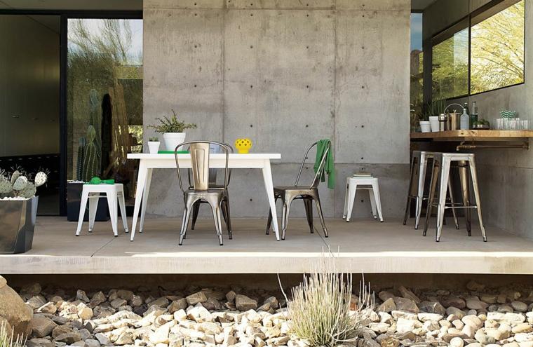 Piante da giardino sempreverdi, arredamento dallo stile industriale con tavolo da pranzo bianco e sedie in metallo