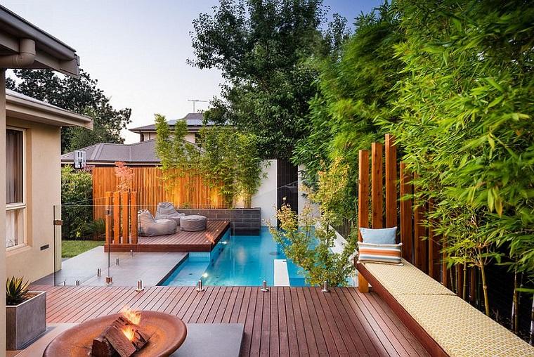 Piante ornamentali da giardino con piscina e pavimento in legno, recinzioni con travi e ringhiera di vetro