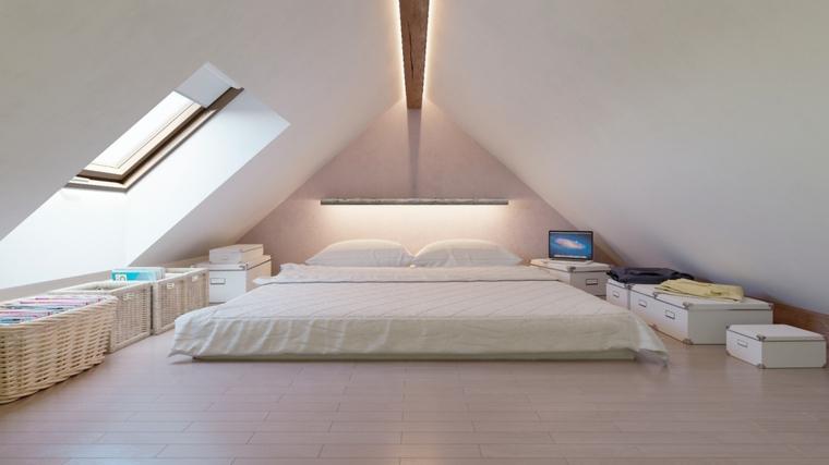 luminosa camera con un grande letto futon, alcune ceste in vimini e bauli bianchi per arredare mansarda moderna