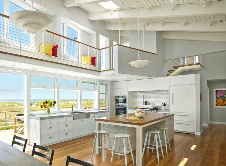 pavimento in legno chiaro, mobili della cucina a vista bianchi, isola con cassetti e sgabelli