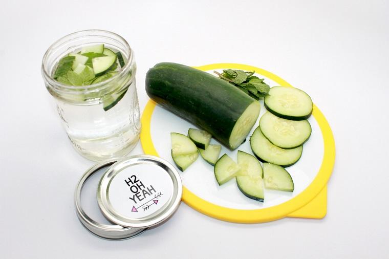 Acqua detox brucia grassi, barattolo di vetro con una bevanda aromatizzata al cetriolo e menta