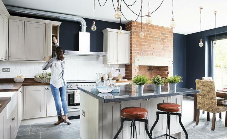 esempio di arredamento cucina moderna con isola e sgabelli vintage, mattoni a vista e mobili bianchi