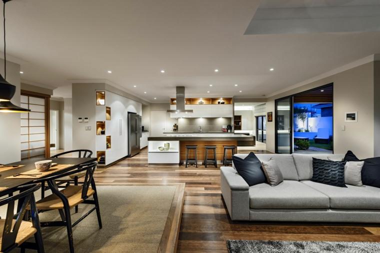pavimento parquet, divano grigio, mobili della cucina bianchi con isola e sgabelli neri, open space cucina soggiorno moderno