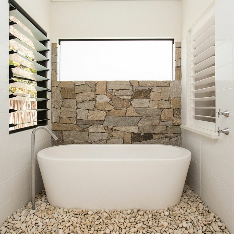 piccolo bagno con parete in pietra e vasca bianca con rubinetto in acciaio inox