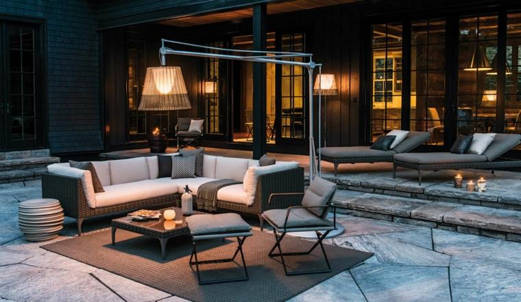 Arredamento da esterno con un divano di rattan e tavolino basso, lampada da terra con paralume abbinato
