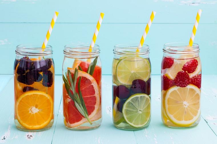 Acqua aromatizzata alla frutta, servita in quattro barattoli di vetro con cannucce