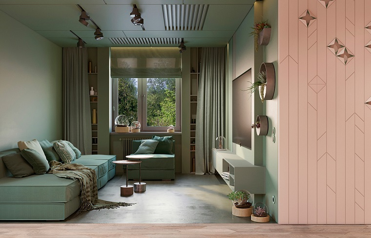 Arredare soggiorno con un divano in tessuto di colore verde e porta scorrevole di legno rosa