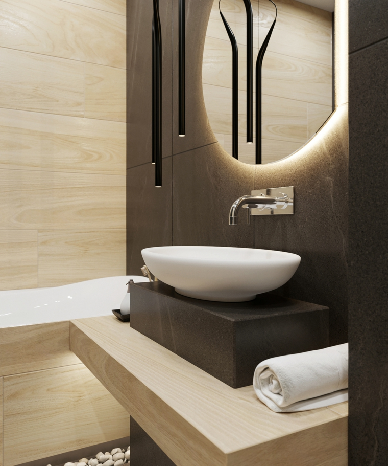 Piastrelle bagni moderni di colore nero, lavandino da appoggio e specchio rotondo con retroilluminazione