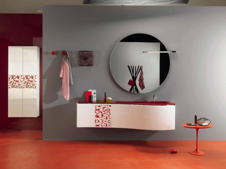Rivestimenti bagni esempi con piastrelle di colore arancione, parete grigia con specchio rotondo
