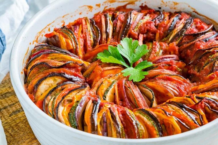 Ratatouille in una pirofila rotonda con verdure tagliate a rondelle, secondi piatti estivi per cena