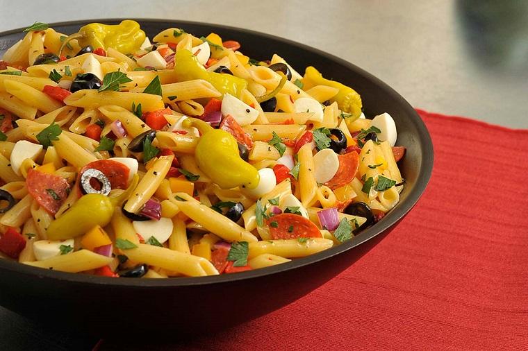 Ricette veloci cena con pasta penne alle verdure, condimento tagliato e pezzettini e servito in piatto di colore nero