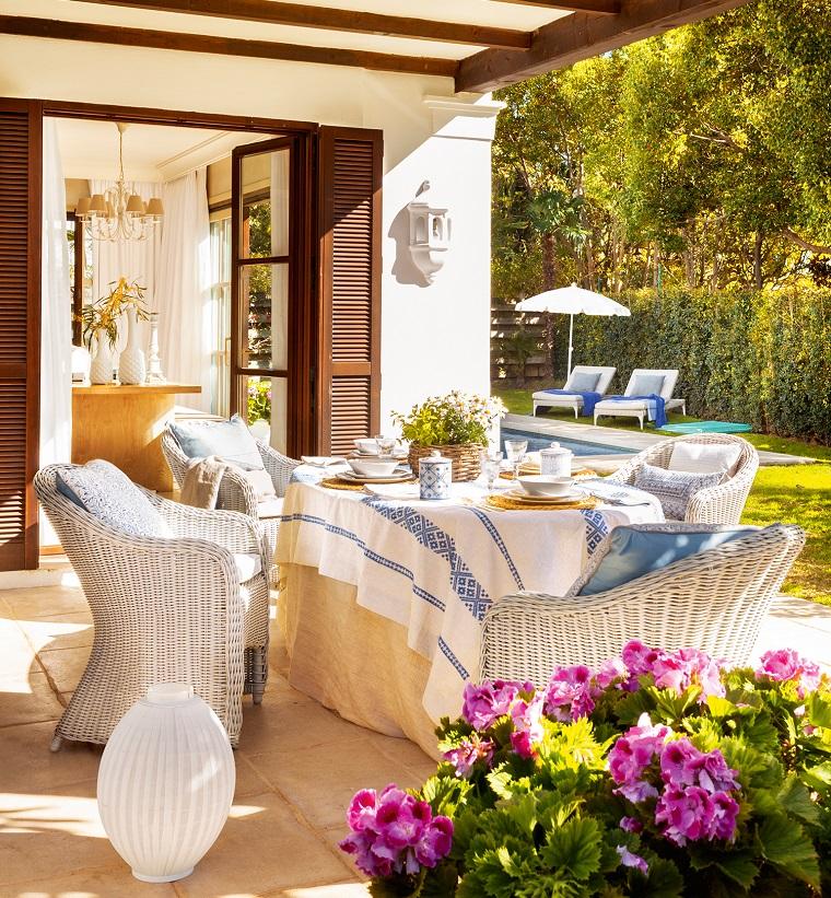 Piante da giardino fiorire, arredamento con sedie in rattan di colore bianco e un tavolo con tovaglia greca