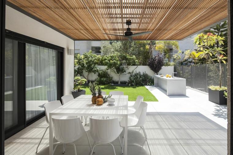Un'idea con prato, piante da giardino e set tavolo da pranzo colore bianco