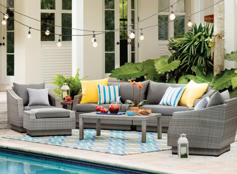 Set di mobili in rattan di colore grigio, decorazioni con tanti cuscini colorati e luminaria appesa