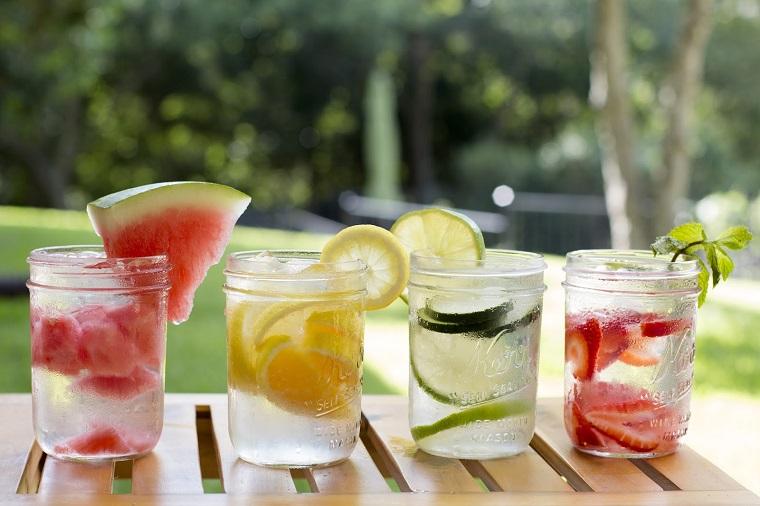 Barattoli di vetro con acqua aromatizzata alla frutta, da condire con foglie di menta