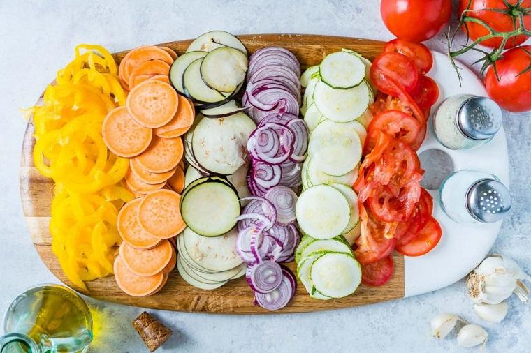 Verdure tagliate su un tagliere di legno, ricette veloci cena da preparare al forno