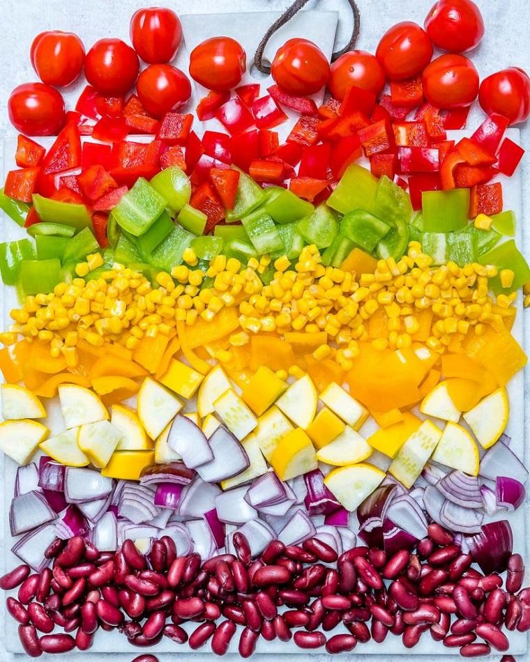Idee cena veloce con tante verdure tagliate a pezzettini su un tagliere di colore bianco