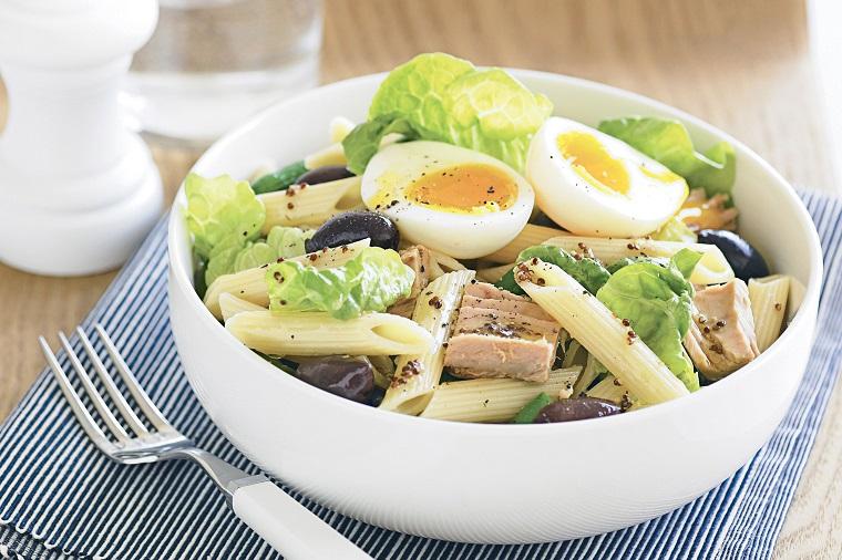 Lattuga con uovo sodo e tonno in scatola scolato, pasta fredda con olive nere in piatto tondo