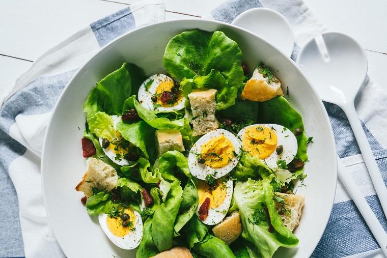 Piatti estivi veloci con lattuga, uova sode con pezzettini di carne e pane