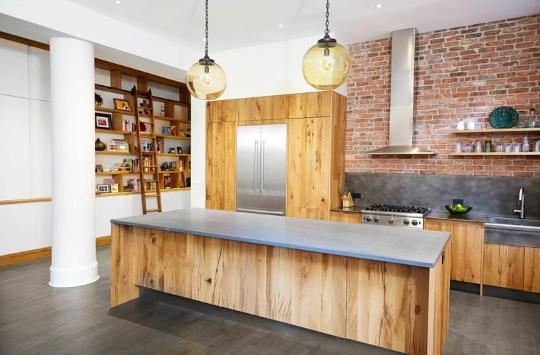 originale arredamento per una cucina open space con isola in legno, cappa in acciaio e pareti in pietra