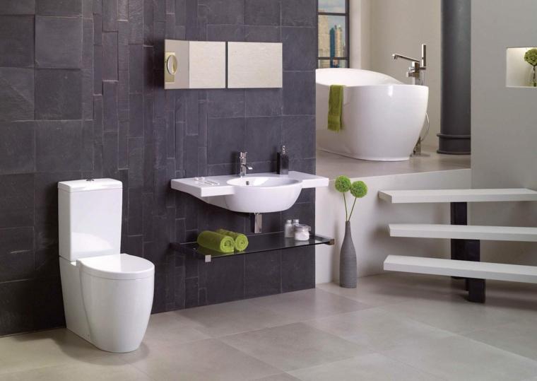 Rivestimento bagno moderno con piastrelle di colore nero, vasca ovale con rubinetto alto da terra