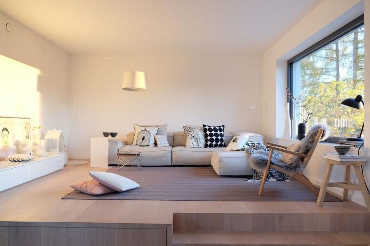 Arredare soggiorno con un divano morbido di colore beige e mobile bianco da terra