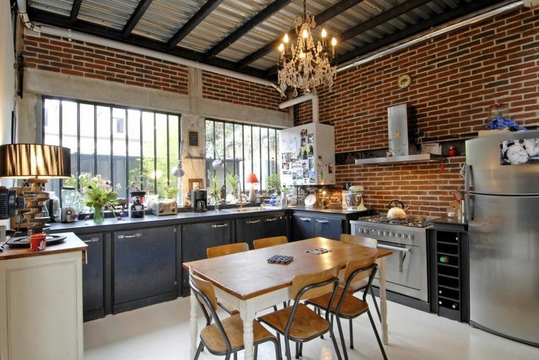 cucina a l con mobili scuri ed elettrodomestici in acciaio, lampadario elegante e interni in pietra
