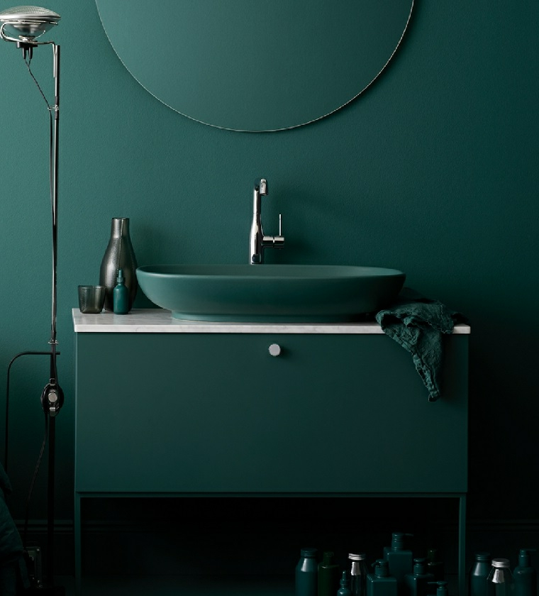 Mobile di legno colore verde petrolio con lavabo in appoggio e specchio rotondo