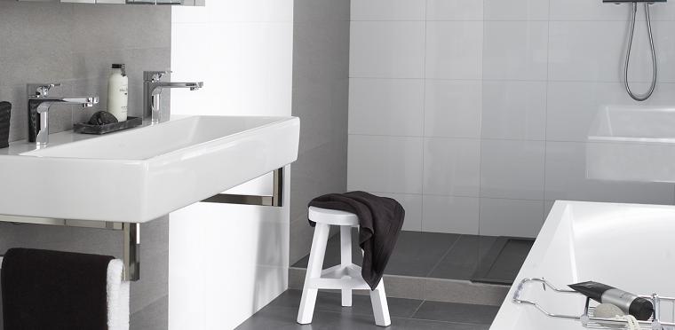 Rivestimento bagno con piastrelle bianche, arredamento con vasca e lavabo monoblocco