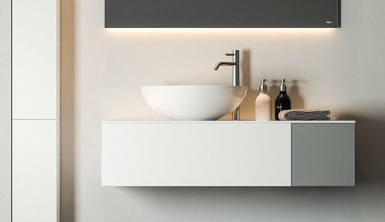 Idee bagno moderno piccolo con un mobile appeso e lavandino da appoggio, specchio con retroilluminazione