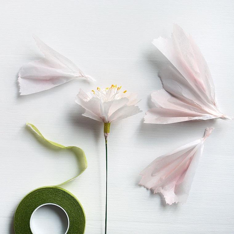 Fiori di carta crespa con petali di colore bianco e pistilli di filo bianco da cucina